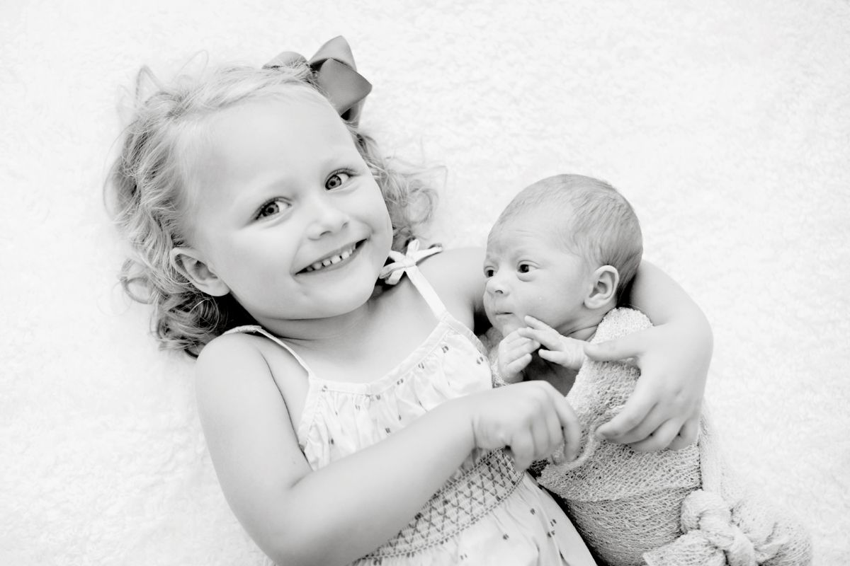 Black and white photo of big sister cuddling baby taken from above